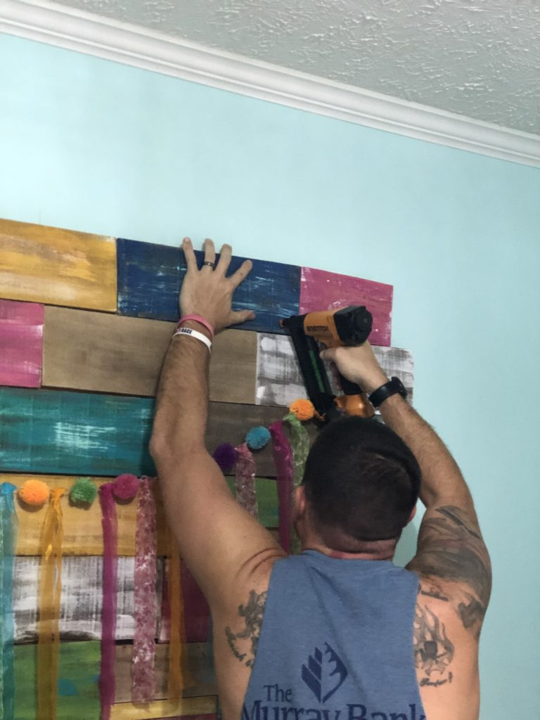 Nailing painted boards for Pallet Wall Colorful Backdrop by Southern ADOORnments