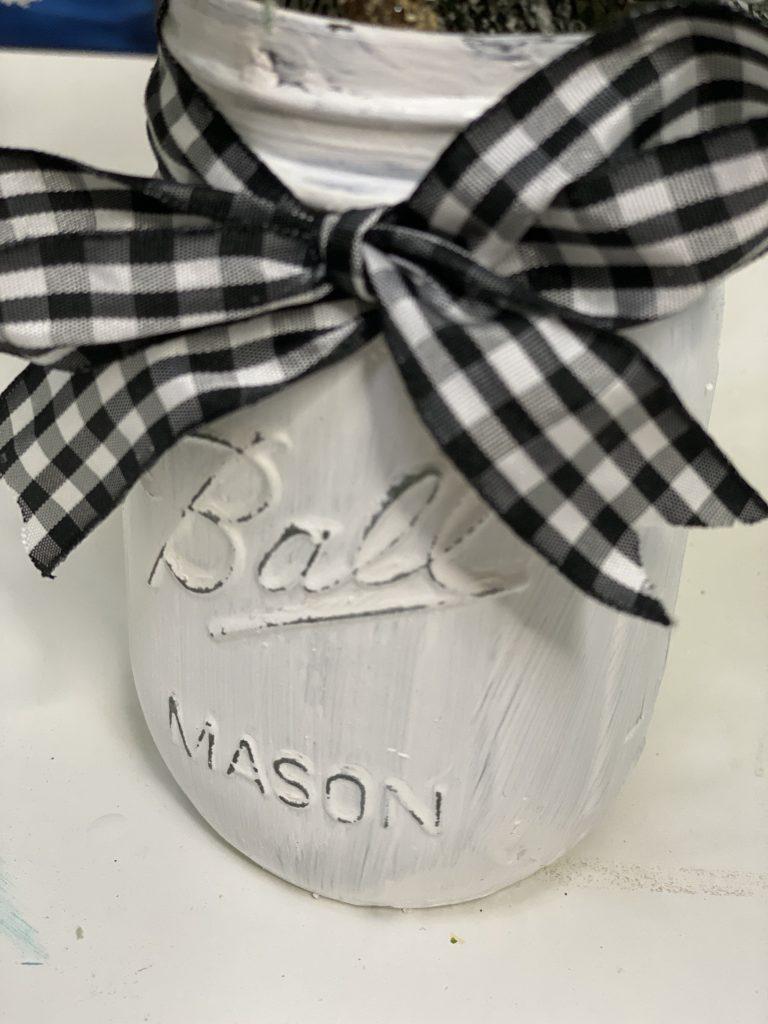 Closeup of Painted Christmas Mason Jar with Buffalo Plaid Ribbon by Southern ADOORnments