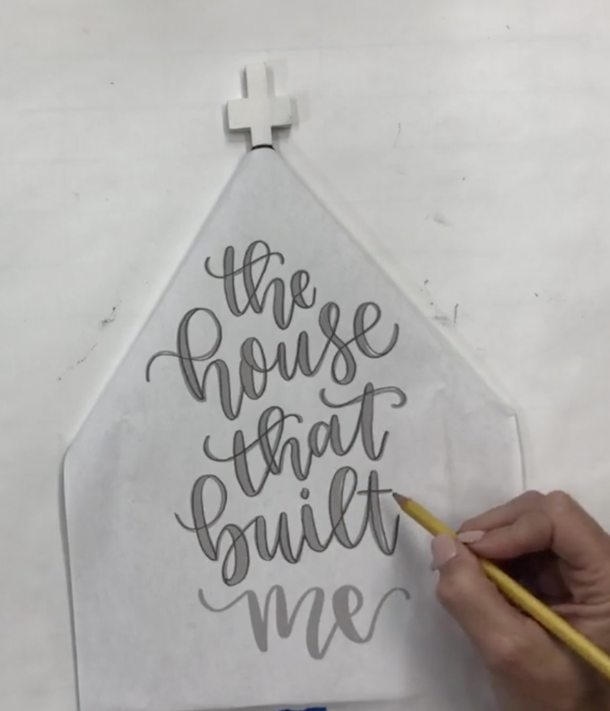 Danielle Stringer tracing hand lettering template on a Souther Adoornments door hanger