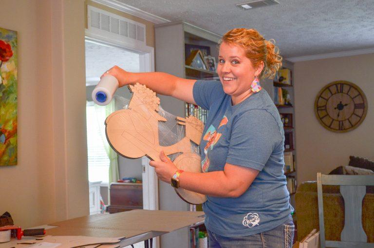 Tamara Wrapping a Southern A-Door-nment Door Hanger in Protective Wrap for Shipping Prep